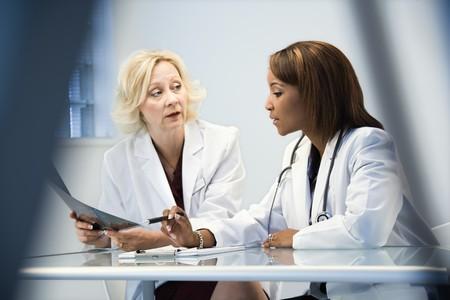 """Weibliche Ã""""rzte discussing Patienten X-Ray-Filme. Lizenzfreie Bilder"""