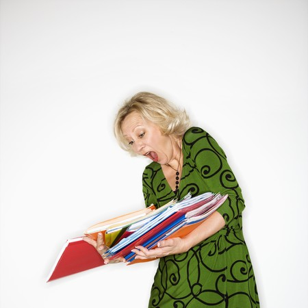clumsiness: Caucasian middle aged businesswoman dropping stack of folders. Stock Photo