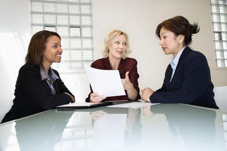 Drei Geschäftsfrauen am habend Tagungs- und discussing schreibarbeit schreibtisch sitzend.  Lizenzfreie Bilder