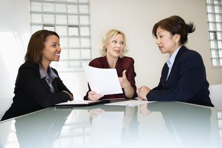Three businesswomen sitting at office desk having meeting and discussing paperwork.
