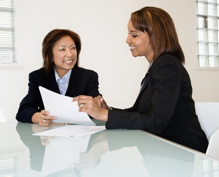 review: Two businesswomen sitting at office desk having meeting and discussing paperwork. Stock Photo