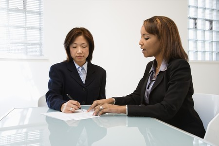 Businesswomen discussing paperwork at office desk. Stock Photo