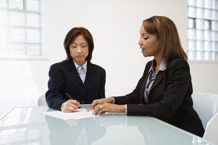 firmando: Empresarias discutiendo el papeleo en el escritorio de la Oficina. Foto de archivo
