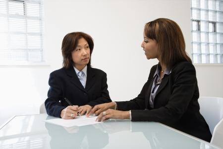 Businesswomen discussing paperwork at office desk. Standard-Bild