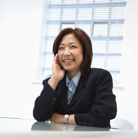 Portrait of Asian businesswoman sitting at desk smiling.