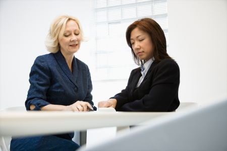 Two businesswomen sitting at office desk looking and talking over papers. Stock Photo
