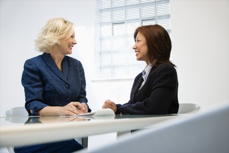 Two businesswomen sitting at office desk looking at eachother smiling.