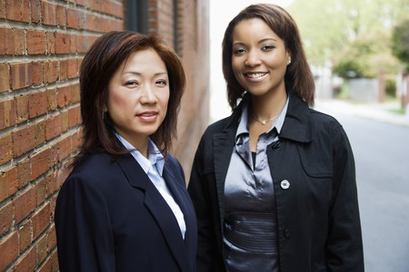 Portrait of two businesswomen standing on street sidewalk.