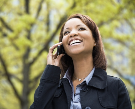 woman on phone: African American young woman talking on mobile phone smiling and laughing.