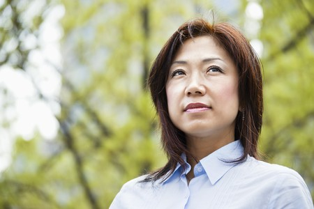 thinking woman: Portrait of an Asian woman outdoors. Stock Photo