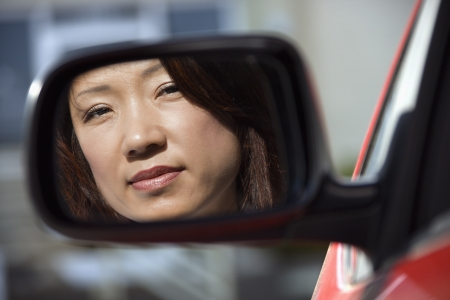 mirror: Reflection of Asian woman in side view car mirror.