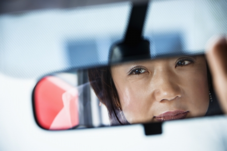 Reflection of Asian woman in rearview car mirror.