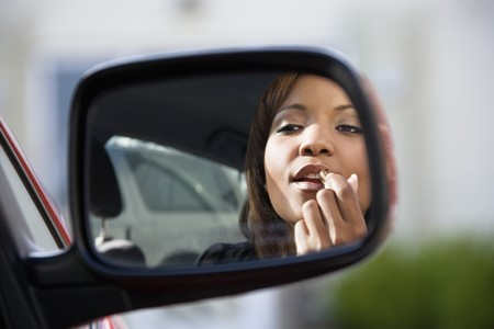Young African American woman applying lipstick looking at reflection in car mirror. photo