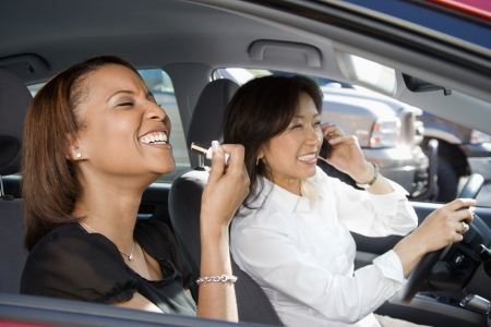 Women distracted and laughing in car with cellphone and cosmetics.