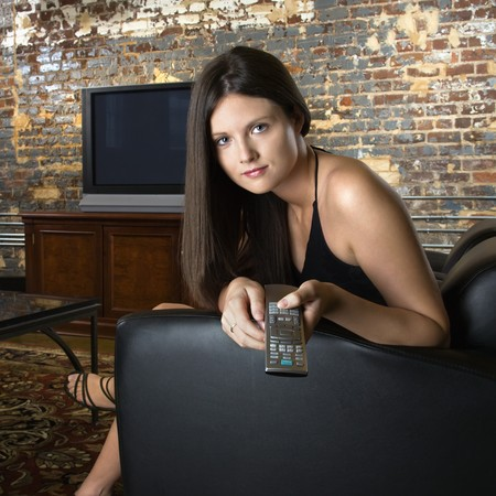 Pretty Caucasian young woman sitting in chair pointing remote control and pushing button. photo