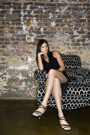 furnished: Pretty young Caucasian woman wearing black dress sitting in patterned chair.