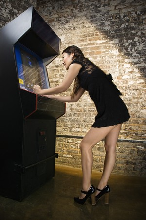 Attractive young woman standing wearing short dress playing video arcade game. Stock Photo - 6908260