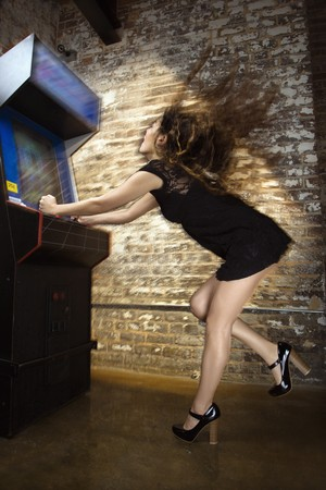 Attractive young woman standing wearing short dress playing video arcade game with hair flying out behind her.