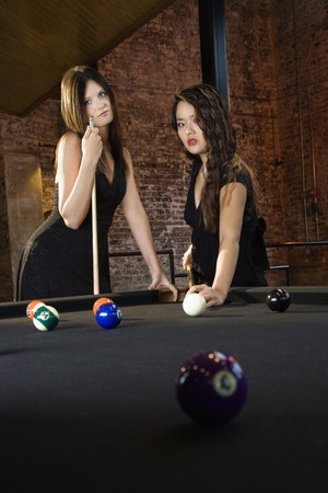 Two attractive young women playing billiard game. photo