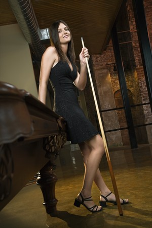 Attractive young woman standing by pool table holding pool cue. photo