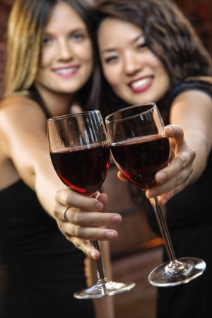woman drinking wine: Two attractive young women toasting wine glasses with red wine and smiling.