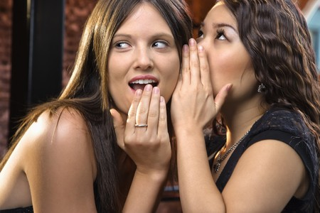 Attractive young woman whispering secret in friend's ear.