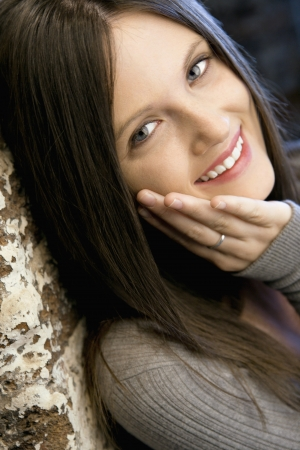 Portrait of pretty young Caucasian woman leaning against brick wall smiling. Stock Photo - 6924796