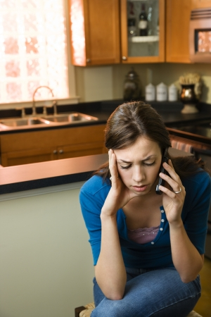 Pretty Caucasian young woman talking on cellphone looking upset. Stock Photo