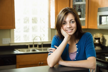 Pretty Caucasian young woman smiling in kitchen. Stock Photo - 6924712