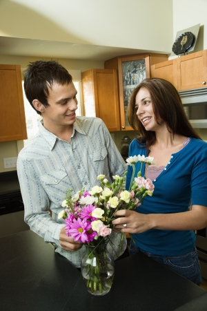 Young couple in kitchen arranging flowers in vase. Stock Photo - 6924791