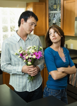 Husband trying to give wife flowers and getting the cold shoulder. Stock Photo - 6924786