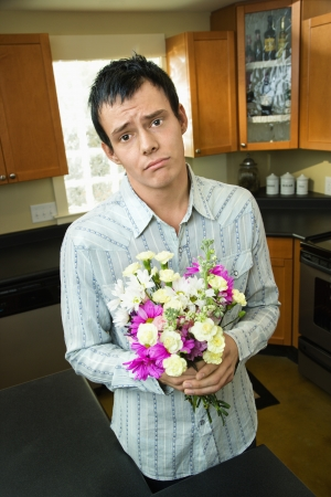 Man holding bouquet of flowers looking sorry and asking forgiveness. Stock Photo - 6924788