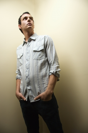 Portrait of young Caucasian man standing with hands in pockets looking up. Stock Photo - 6924737
