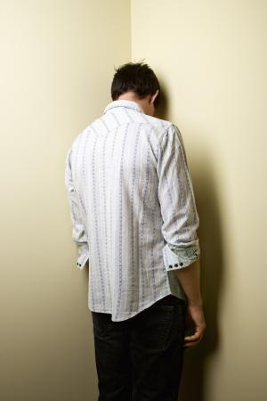 in trouble: Joven de pie con la cabeza en la esquina. Foto de archivo