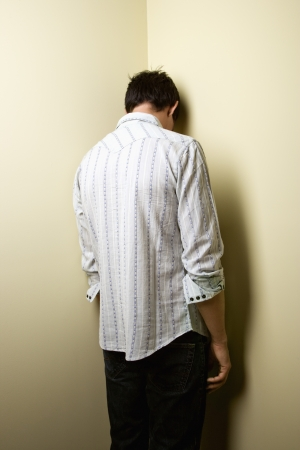 man rear view: Young man standing with head in corner.