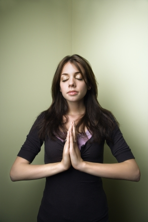 Portrait of pretty young brunette woman standing with hands in prayer and eyes closed. Stock Photo - 6924745