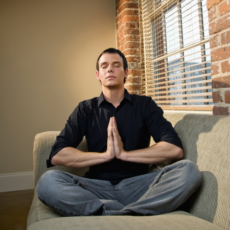 Young Caucasian man sitting on sofa meditating. Stock Photo - 6924792