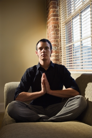 Young Caucasian man sitting on sofa meditating. Stock Photo - 6924785