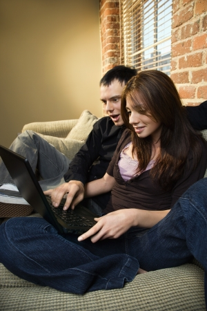 Young Caucasian couple at home looking at computer smiling. Stock Photo - 6924798