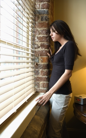 Young Caucasian woman standing at window looking out. Stock Photo - 6924750