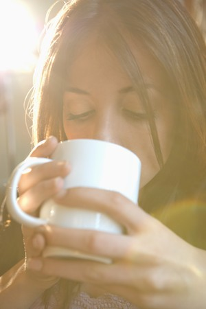 Young Caucasian woman drinking from coffee cup. photo