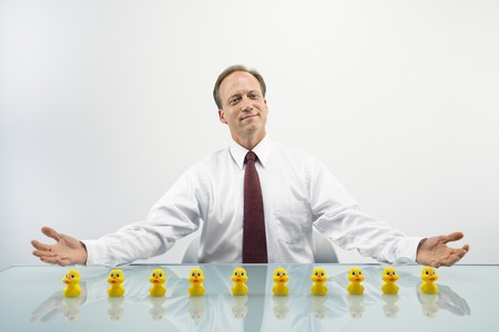 Portrait of middle aged  Caucasian businessman sitting at desk with ducks in a row. Standard-Bild