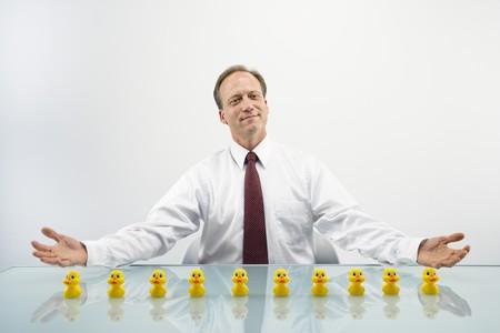 Porträt von Mitte zwischen kaukasischen Businessman sitting at Desk mit Enten in einer Reihe.  Lizenzfreie Bilder