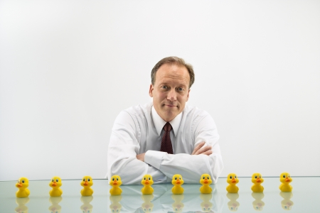 Portrait of middle aged Caucasian businessman sitting at desk with ducks in a row.