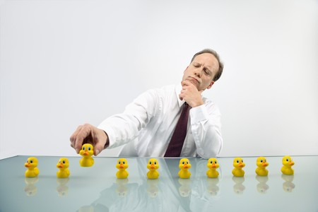 row: Portrait of middle aged  Caucasian businessman sitting at desk with ducks in a row. Stock Photo