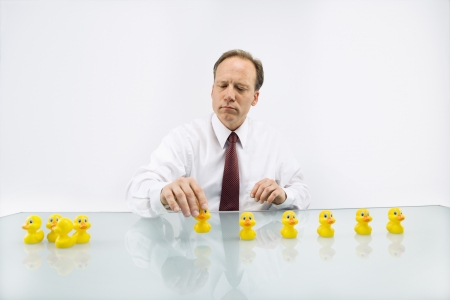 row: Portrait of middle aged  Caucasian businessman sitting at desk putting ducks in a row. Stock Photo
