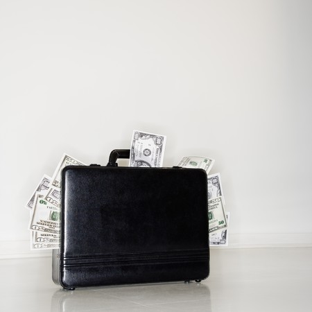 corporate greed: Business briefcase overflowing with cash money.