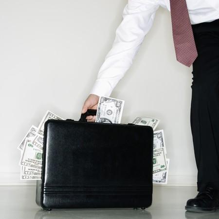 money laundering: Caucasian centrale invecchiato imprenditore che trasportano la valigetta traboccante di denaro.