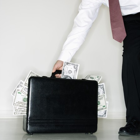corporate greed: Caucasian middle aged businessman carrying briefcase overflowing with money.