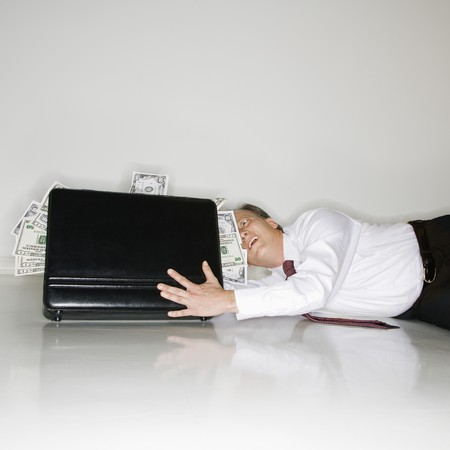 Caucasian middle aged businessman grabbing at briefcase overflowing with money. photo